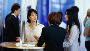 three businesswomen discussing services at an tradeshow exhibition